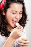 吃酸奶的新美丽的妇女 库存图片