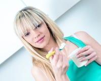 吃酸奶的纵向少妇 免版税库存图片
