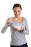吃酸奶的年轻偶然妇女。 库存图片