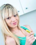 吃酸奶食物的微笑的妇女 免版税库存照片