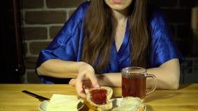 吃面包和果酱,饮用的热的茶的少妇 股票录像
