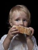 吃面包的饥饿的孩子 免版税库存照片