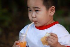吃面包的年轻男孩 库存照片