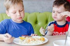 吃面团用炸肉排的两个男孩 免版税库存照片