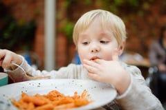 吃面团的逗人喜爱的小孩男孩用意大利语户内餐馆 库存图片