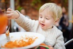 吃面团的逗人喜爱的小孩男孩用意大利语户内餐馆 库存照片