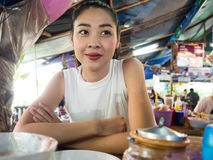 吃面条的亚裔妇女在泰国地方餐馆 免版税图库摄影