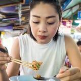 吃面条的亚裔妇女在泰国地方餐馆 库存图片