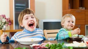 吃食物的两个愉快的孩子 免版税库存照片