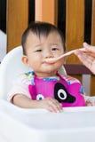 吃食物的亚裔逗人喜爱的婴孩 库存照片