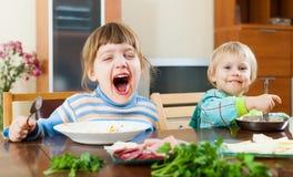 吃食物的女婴在桌上 免版税图库摄影
