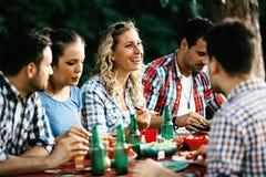 吃食物的小组愉快的人民户外 库存图片