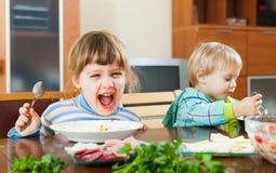 吃食物的愉快的孩子 免版税库存照片
