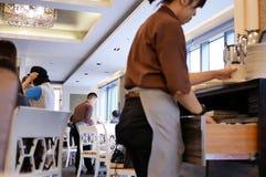 吃食物的排序板材的人的行动和工作者和强迫退场在餐馆里面 库存图片