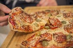 吃食物 人手特写镜头采取切片意大利辣味香肠的 免版税库存照片