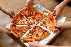 吃食物 采取薄饼切片的人们 朋友休闲,快速的F 免版税库存照片