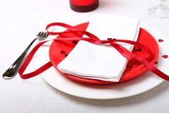 吃饭的客人周年庆祝的红色和白色桌设置 图库摄影
