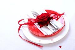 吃饭的客人周年庆祝的红色和白色桌设置 免版税图库摄影