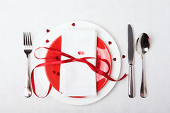 吃饭的客人周年庆祝的红色和白色桌设置 免版税库存图片