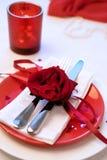 吃饭的客人周年庆祝的红色和白色桌设置 免版税库存照片