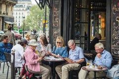 吃饭的客人学习菜单在Ile圣路易斯的咖啡馆圣里吉斯, 免版税库存图片