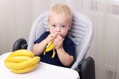 吃香蕉和坐在婴孩椅子的逗人喜爱的一个岁小孩 免版税库存照片