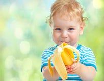 吃香蕉果子的愉快的孩子。健康食物吃概念。 库存图片