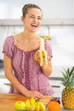 吃香蕉的微笑的少妇在厨房里 库存图片