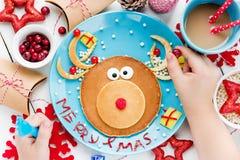 吃驯鹿薄煎饼圣诞节早餐的孩子 库存图片