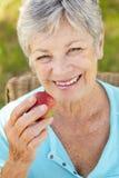 吃高级妇女的苹果 免版税库存照片