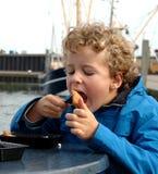 吃鱼港口的男孩 免版税图库摄影
