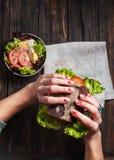 吃鲜美不健康的汉堡的妇女在手上扭转了三明治 免版税库存图片