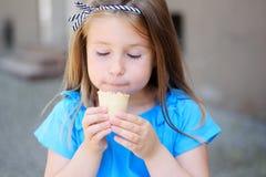 吃鲜美冰淇凌的可爱的小女孩在公园在温暖的晴朗的夏日 免版税库存照片