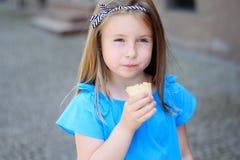 吃鲜美冰淇凌的可爱的小女孩在公园在温暖的晴朗的夏日 免版税图库摄影