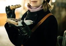 吃鲜美奶蛋烘饼的妇女在圣诞节市场上 免版税库存照片