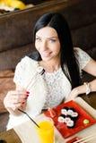 吃鲜美寿司的美丽的深色的少妇的图象有乐趣愉快微笑的坐在餐馆&看照相机 库存照片