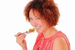 吃鲜美沙拉的微笑的女孩 库存照片