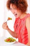 吃鲜美沙拉的恼怒的女孩 免版税库存图片