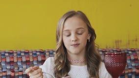 吃鲜美点心和微笑对照相机的愉快的女孩 迟缓地 股票视频