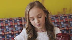 吃鲜美点心和微笑对照相机的愉快的女孩 迟缓地 影视素材