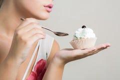 吃鲜美甜点心用黄油c的可爱的白肤金发的妇女 免版税图库摄影