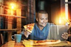 吃鲜美薄饼和读新闻在屏幕上的微笑的人 库存照片