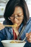 吃鸡蛋面用酥脆猪肉的妇女从筷子和遇见 库存图片