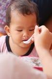 吃龙果子以愉快地的亚裔婴孩 免版税图库摄影