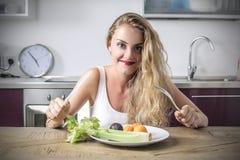 吃水果和蔬菜的微笑的女孩 免版税图库摄影