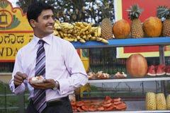 吃水果沙拉的商人在室外摊位 免版税图库摄影