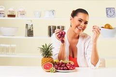 吃从水果钵的年轻美丽的妇女葡萄 库存照片