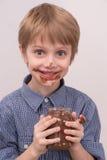吃从瓶子的微笑的孩子巧克力 免版税图库摄影