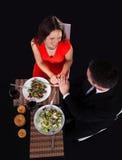 吃年轻的夫妇晚餐用酒 免版税库存图片