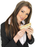 吃年轻的女商人拿着一条健康三文鱼用黄瓜黑面包三明治 免版税库存照片